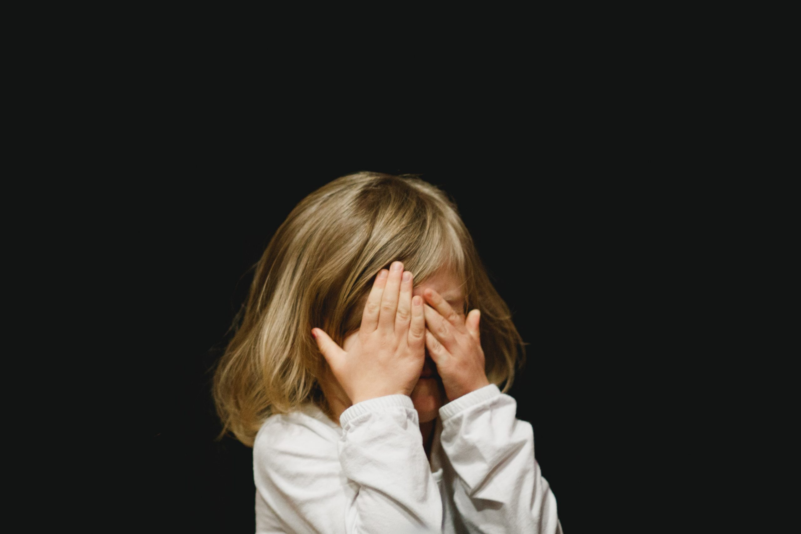 Little girl with hands covering face