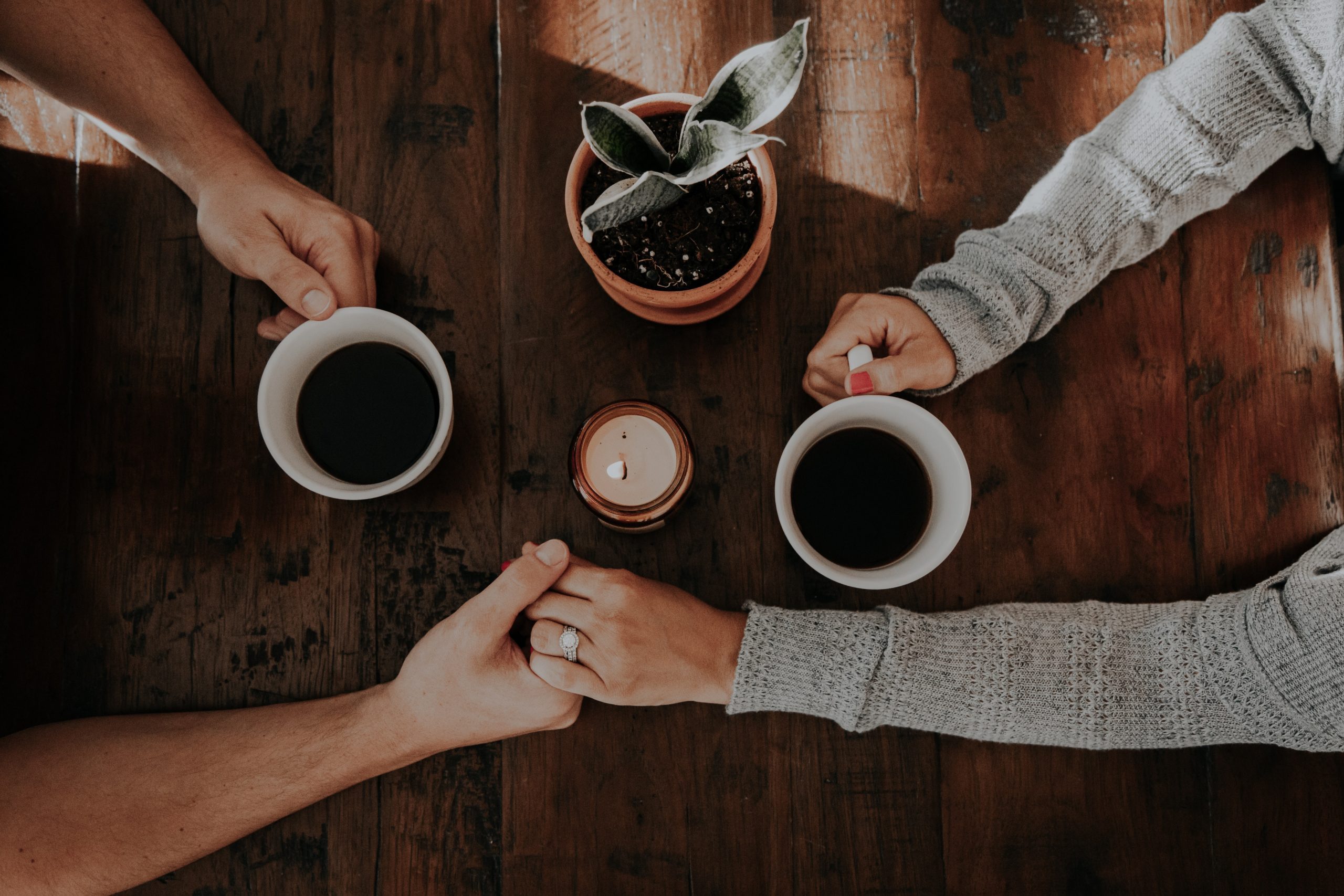 Man and woman holding hands over coffee