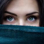 Woman holding scarf across her face