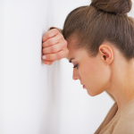 Woman with head against the wall